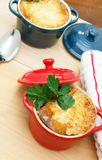 French Onion Soup Gratin. In red and blue pots on table top Royalty Free Stock Photography