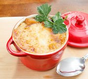 French Onion Soup Gratin. In red and blue pots on table top Royalty Free Stock Photo