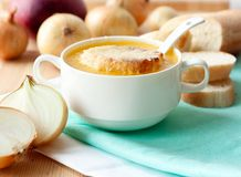 French onion soup in white porcelain bowl. With onion and fresh baguette Royalty Free Stock Photos
