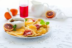 French pancakes. Crepe Suzette with caramel, oranges, blueberries, almonds and hazelnuts. On white table cloth royalty free stock photo