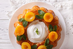 French pastries: Savarin with apricots and mint close-up. horizo Royalty Free Stock Image