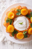 French pastries: Savarin with apricots and mint close-up. vertic Stock Image