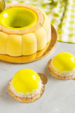 French pastry with yellow mirror glaze. Lemon and coconut mousse dessert with yellow mirror glaze coating. Modern european cake on background. Shallow focus Royalty Free Stock Images