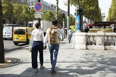 French people boyfriend and girlfriend walking hand in hand on walkway at sidewalk in L'avenue des Champs-Elysees. On September 6, 2017 in Paris, France royalty free stock photography