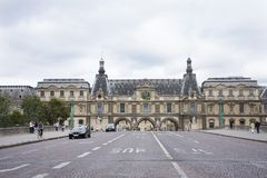 French people driving and biking with travelers walking and traffic road at front of Musee du Louvre. Or the Grand Louvre Museum on September 5, 2017 in Paris Stock Image