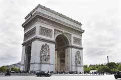Arc de triomphe de l`Etoile or Triumphal Arch of the Star at Place Charles de Gaulle in Paris, France. French people and foreigner travlers walk visit Arc de Royalty Free Stock Photo