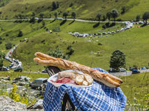 French Picnic. Two fresh French baguettes and salami are on a folding chair on the roadside in mountains Royalty Free Stock Image