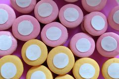 French pink and yellow macarons background, close up Stock Photos