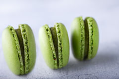 French pistachios macaroons. Three green french pistachios Macaroons on a table Royalty Free Stock Photo