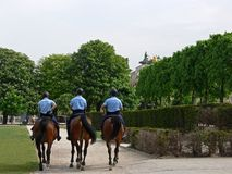 French police. Three policemen on horses riding through a park stock photo