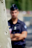French policeman hidden behind a tree. A French policeman watching drivers for using cell-phones. Paris, France Royalty Free Stock Photo