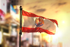 French Polynesia Flag Against City Blurred Background At Sunrise. Backlight Sky Royalty Free Stock Images