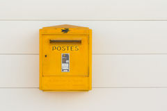 French postal service. A traditional yellow mailbox mounted on a white wall, belonging to the French postal service La Poste royalty free stock photo