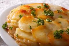 French Potatoes Anna on a white plate macro. horizontal Royalty Free Stock Photo