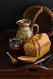 French pound cake. Partially sliced French spice cake displayed with a jar of honey, a pitcher and a basket Stock Image