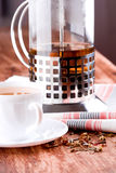 French press and cup of fresh herbal tea. Closeup on wooden table Royalty Free Stock Photography