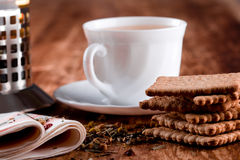 French press, cup of tea and some cookies. French press, cup of fresh herbal tea and some cookies closeup on wooden table Royalty Free Stock Image