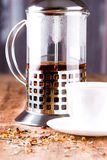 French press with herbal tea. And cup closeup on wooden table Royalty Free Stock Images