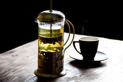 French press. Morning still life: french press with green tea and black coffee cup on the edge of wooden table Royalty Free Stock Photos