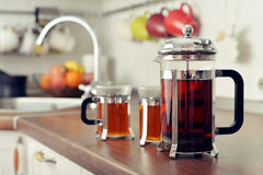 French press with tea and cups Stock Photo