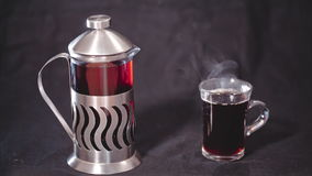 French Press with tea and a transparent Cup of tea on a black background.  stock video footage