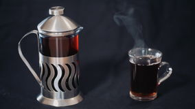 French Press with tea and a transparent Cup of tea on a black background.  stock footage