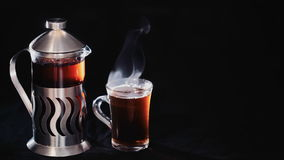French Press with tea and a transparent Cup of tea on a black background.  stock video