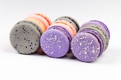 French purple, grey and pink macarons or macaroons, aligned in closeup side view. royalty free stock photography
