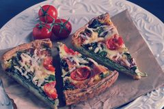 French quiche with eggs, fresh spinach, tomatoes, bacon. And cheese Stock Images