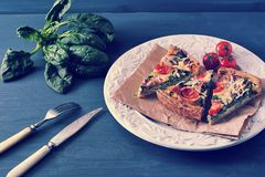 French quiche with eggs, fresh spinach, tomatoes and bacon. Fork and knife Stock Photography