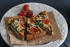 French quiche with eggs, fresh spinach, tomatoes, bacon. And cheese Stock Photo