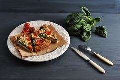 French quiche with eggs, fresh spinach, tomatoes and bacon. Fork and knife Stock Photos