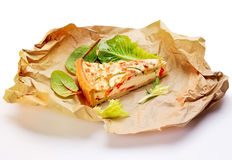 French Quiche with leaves of salad. French breakfast Quiche, leaves of green salad on kraft paper Stock Photography