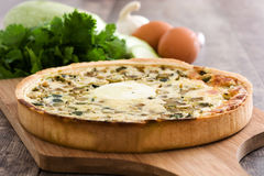 French quiche Lorraine with vegetables on a rustic wooden table Stock Image
