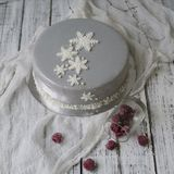 French raspberries mousse cake with New Years decoration - snowflakes and white branches - on a white wooden background royalty free stock photo