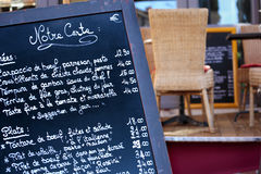 French restaurant Paris France menu board close up, tables and chairs in background. French restaurant Paris France menu board Royalty Free Stock Photos