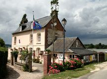 French Riverside House. Riverside Village House in Normandy France, with flag flying on a flagpole and stormy clouds in the background Royalty Free Stock Photography