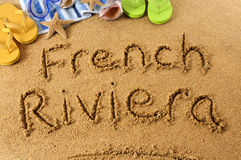 French Riviera beach writing. French Riviera : the words French Riviera written on a sandy beach, with scuba mask, starfish and flip flops Stock Image