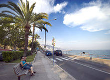 French riviera in Menton. Mother and son sitting on a bench at the coastal road of French Riviera (Côte d'Azur) in Menton, France Stock Photos