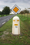 French road sign and bollard. With road and trees in background stock image