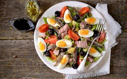 French salad Nicoise with tuna, boiled potatoes, egg, green beans, tomatoes, dried olives, lettuce and anchovies. Royalty Free Stock Photo