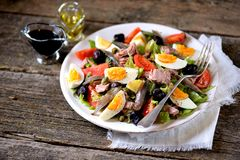 French salad Nicoise with tuna, boiled potatoes, egg, green beans, tomatoes, dried olives, lettuce and anchovies. Stock Photography