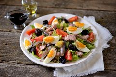 French salad Nicoise with tuna, boiled potatoes, egg, green beans, tomatoes, dried olives, lettuce and anchovies. Stock Photos