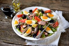 French salad Nicoise with tuna, boiled potatoes, egg, green beans, tomatoes, dried olives, lettuce and anchovies. Stock Photo