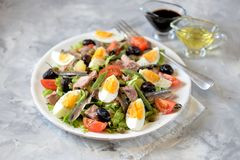 French salad Nicoise with tuna, boiled potatoes, egg, green beans, tomatoes, dried olives, lettuce and anchovies. Royalty Free Stock Photos