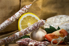 French salami close-up with garlic. French salami close-up on wooden table stock photography