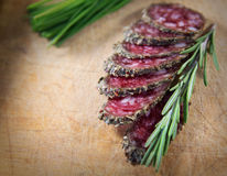 French salami with rosemary. French meat sliced with rosemary royalty free stock image