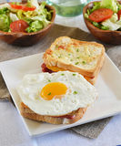 French sandwich croque-monsieur with green salad. On a white plate royalty free stock images
