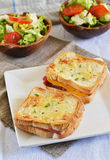 French sandwich croque-monsieur with green salad. On a white plate royalty free stock photo