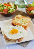 French sandwich croque-monsieur with green salad. On a white plate stock photography